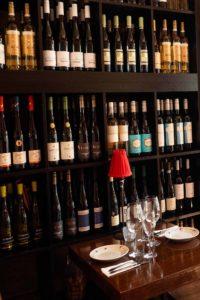 gedeckter Tisch vor einem Regal mit Weinflaschen